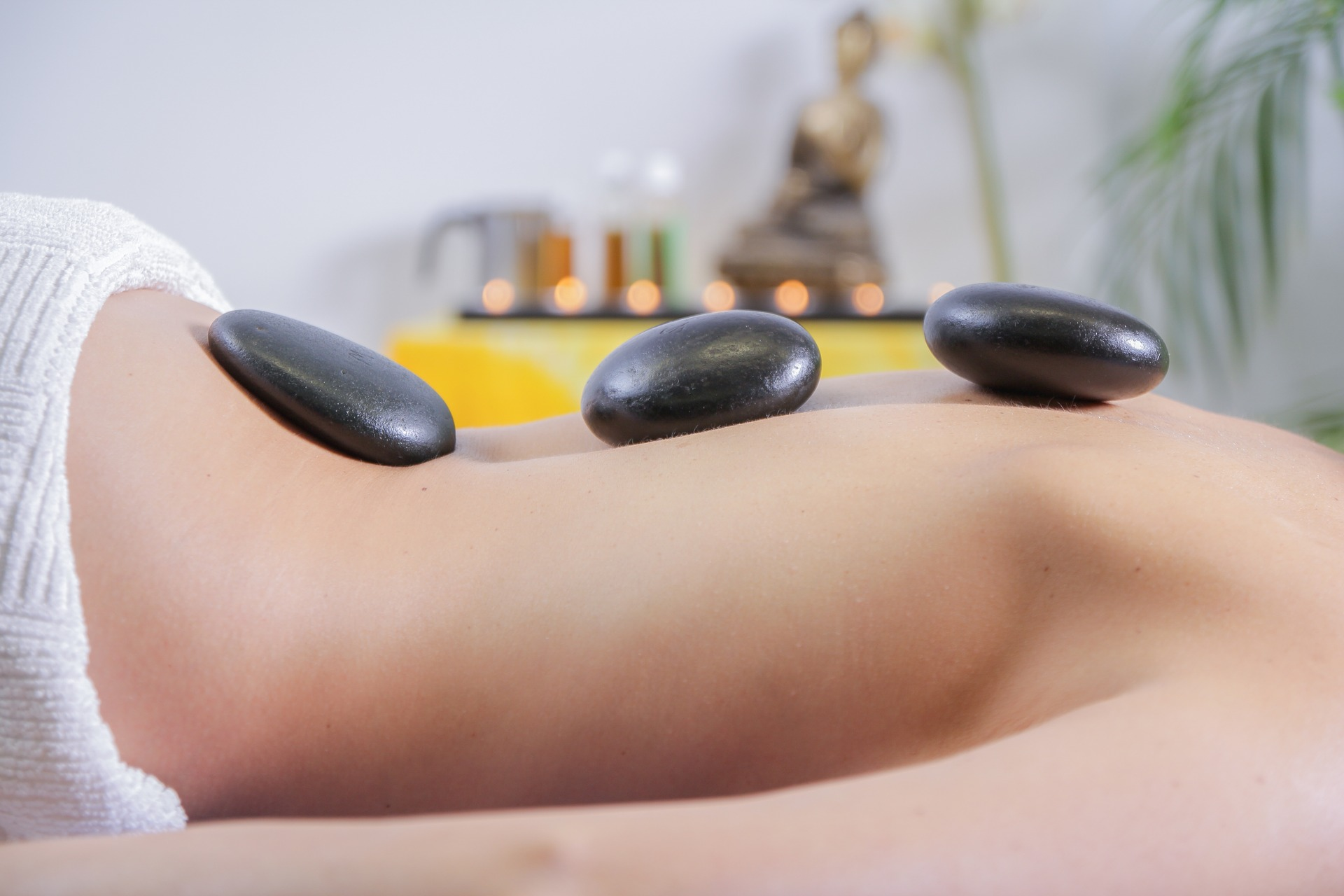 woman lying face down with black rocks on her back as part of hot stone therapy